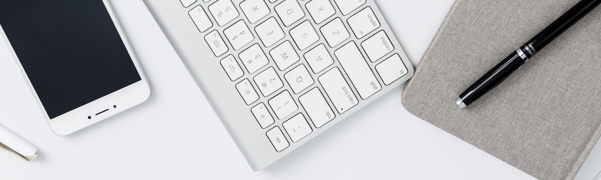 Een smartphone, toetsenbord en blocknote
